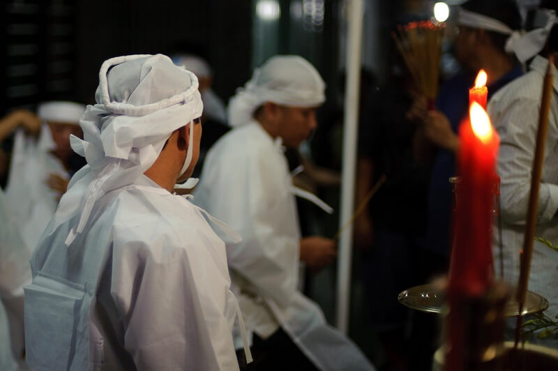 family members in funeral costume during pray